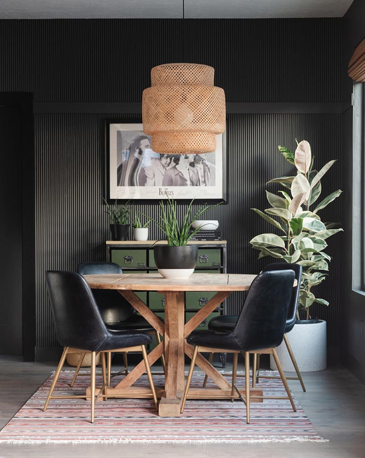 Vignette of a dark bronze dining room with fluted accent wall.