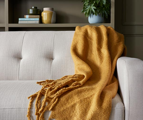 Warm yellow blanket draped over couch.