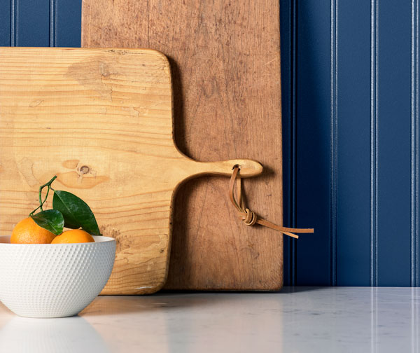 Wooden cutting boards and bowl of oranges in front of wall painted Commodore SW 6524.