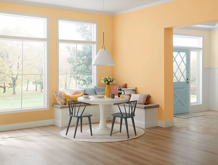 yellow kitchen filled with natural light and a dining nook.
