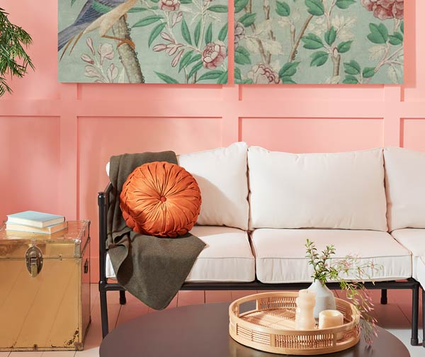 Jovial porch detail image with white couch, gold chest side table, round brown coffee table and green nature paintings on the wall..