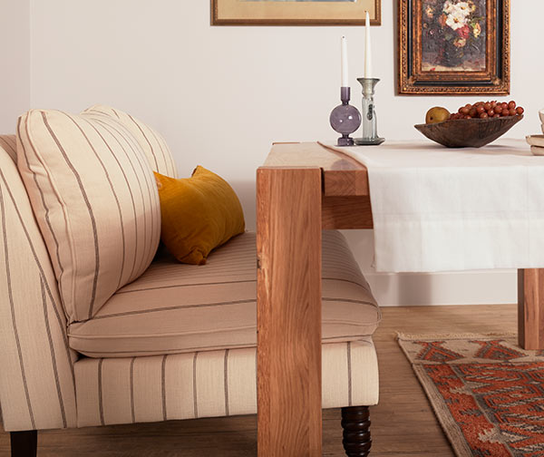 Close up of Linen couch and corner wooden dining table