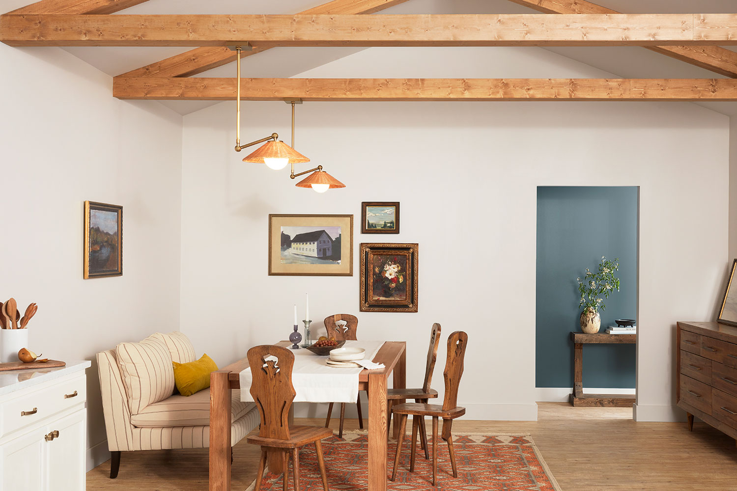 Modern Belgian styled dining room with rustic wood table and exposed wooden beams on ceiling, walls are Eider White SW 7014