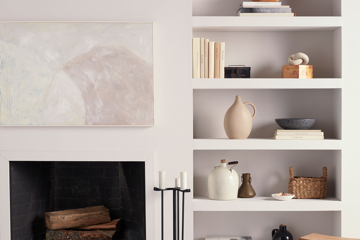 Eider White SW 7014 walls with minimal fireplace and built in shelves decorated with modern vases, art, and books