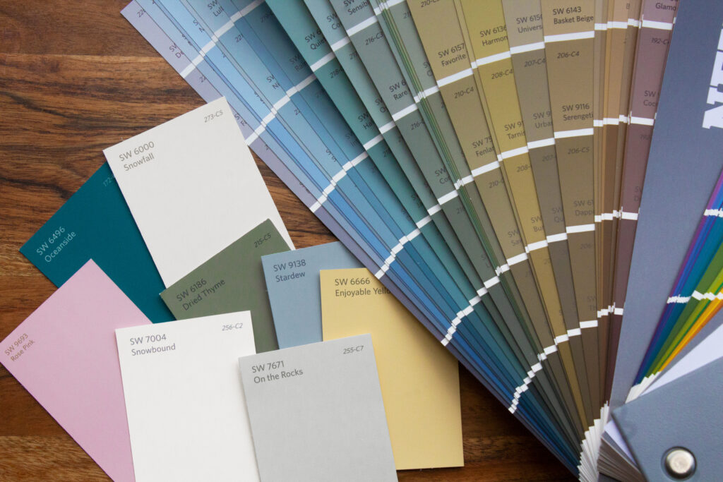A Sherwin-Williams paint strip fan deck next to individual color chips.