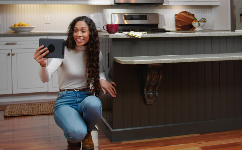 Woman bent down taking a selfie showing off her kitchen island painted in Urbane Bronze SW 7048.
