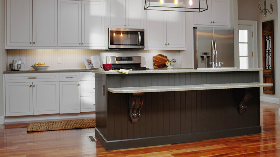 A tuxedo kitchen featuring white cabinets and a kitchen island with cabinets painted in Urbane Brinze SW 7048.
