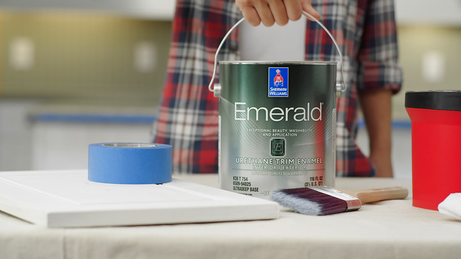 A woman holding a can of Emerald paint.