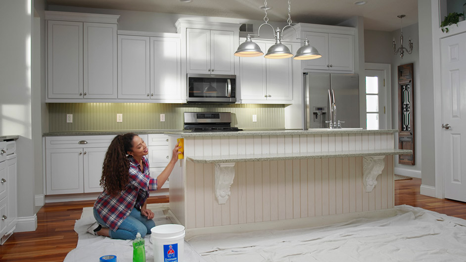 A woman cleaning the surface of her kitchen island.
