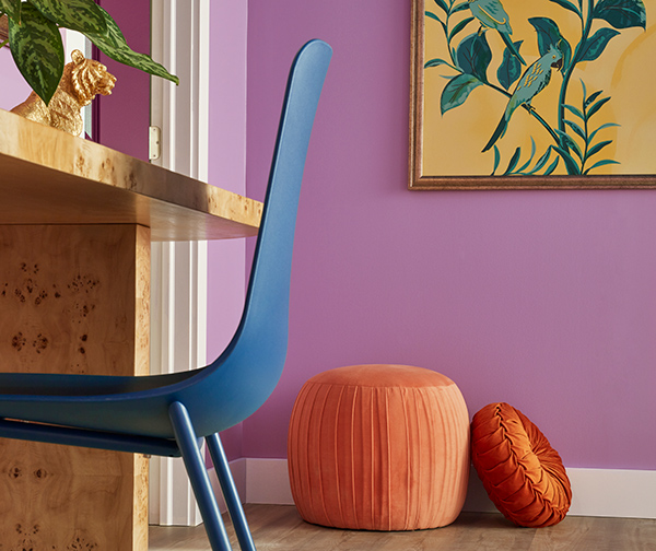Close up of blue desk chair with orange floor pouf and pillow up against Novel Lilac SW 6839 Painted wall in the background