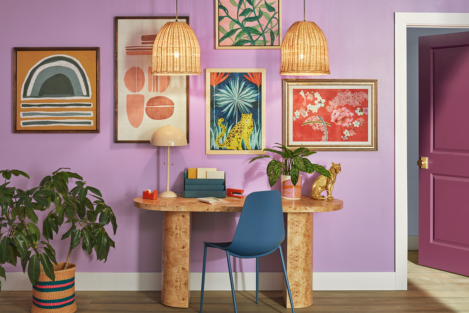 Art deco style wood desk centered on Novel Lilac SW 6839 painted wall, decorated with colorful ectectic paintings accompanied by wicker light fixtures and plants.