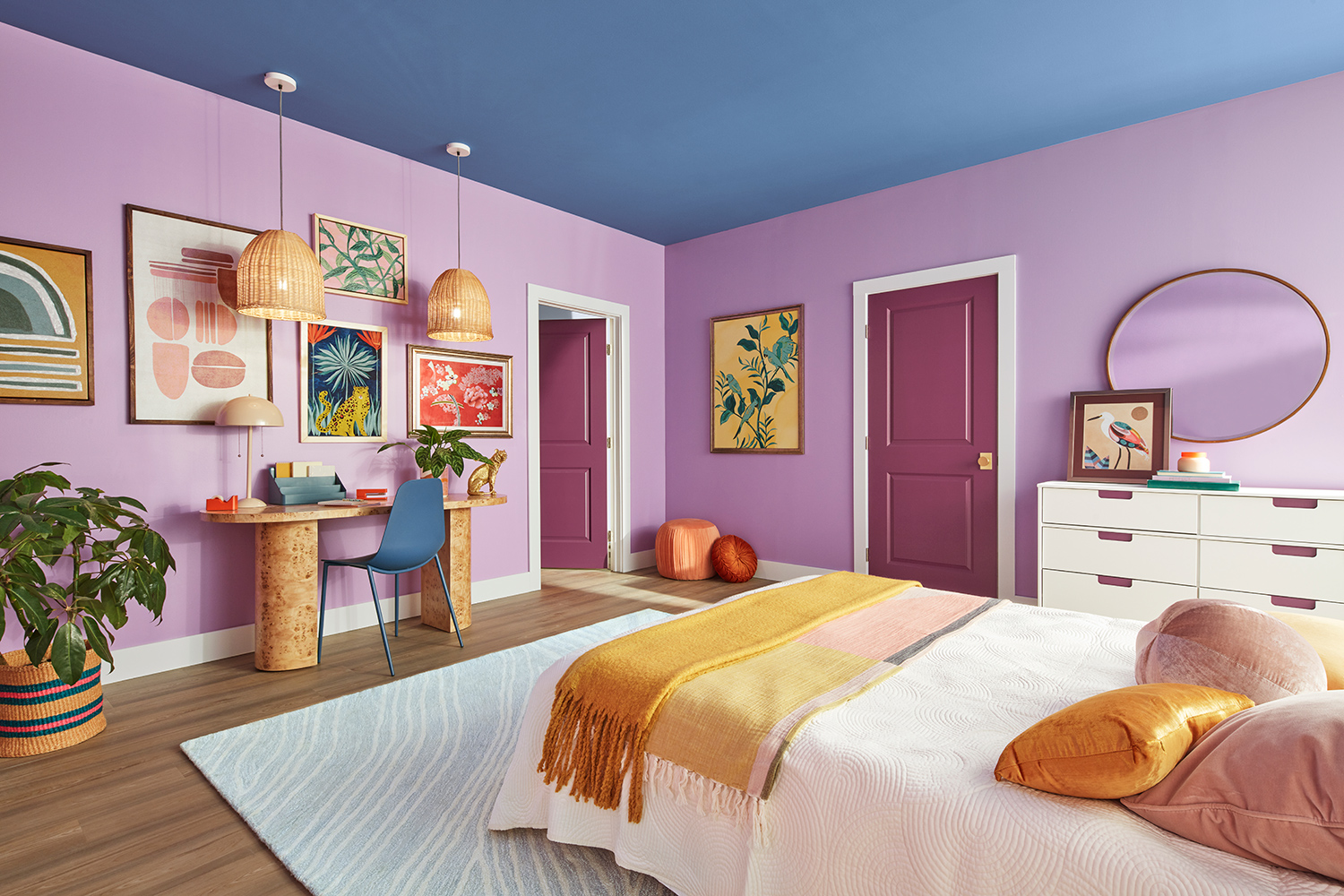 Bedroom image with colorful eclectic wall decor, pants and wicker light fixtures. Walls painted Novel Lilac SW 6839, Ceiling painted Perfect Periwinkle SW 9065, Doors painted Juneberry SW 6573