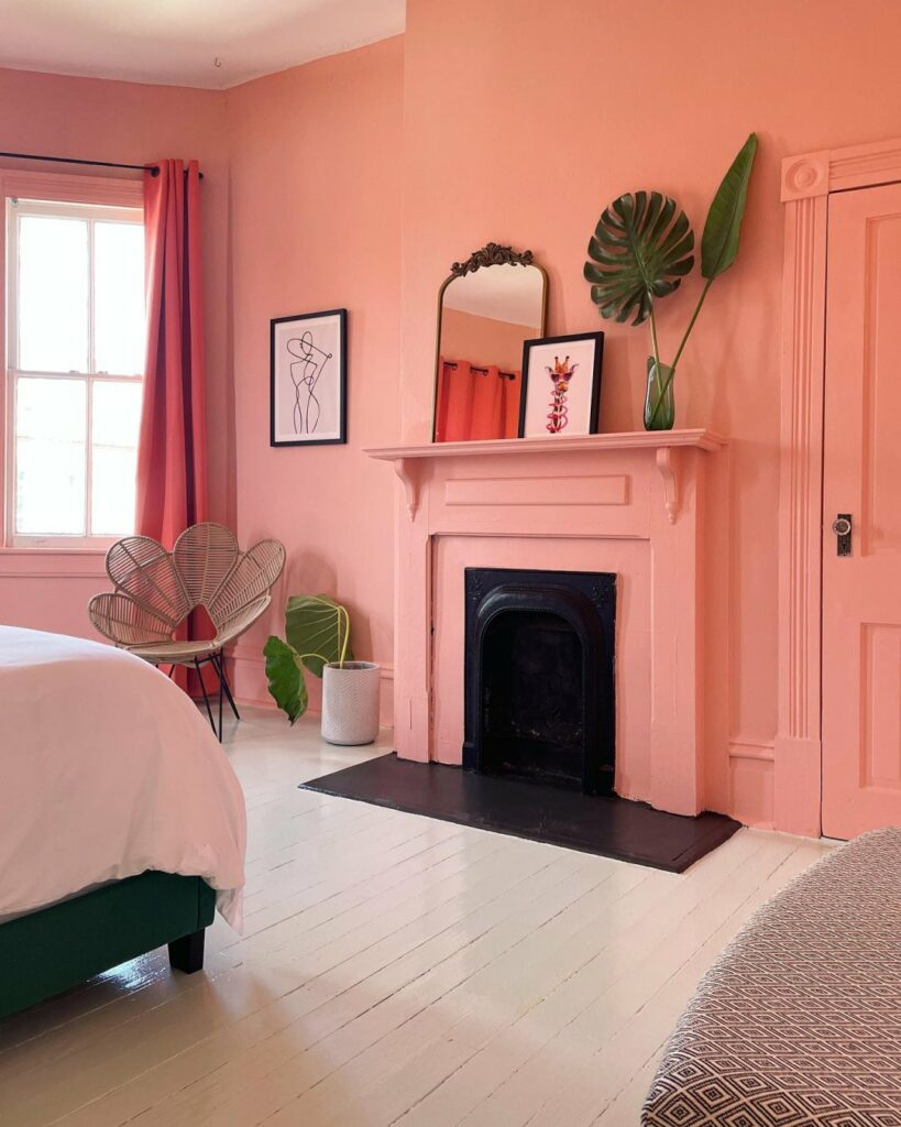 Monochromatic bedroom with walls, trim, door, and fireplace mantel painted in a bright, joyful salmon color from Sherwin-Williams called Rachel Pink SW 0026.