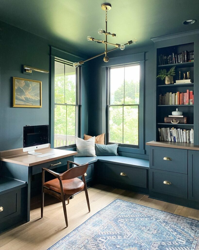 Monochromatic home office with walls, window trim, cabinets, and ceiling painted in a deep, dramatic blue-green color from Sherwin-Williams called Mount Etna SW 7625.