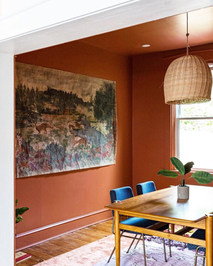 Monochromatic, midcentury modern dining room with walls, trim, and ceiling painted in an earth tone terracotta color from Sherwin-Williams called Cavern Clay SW 7701.