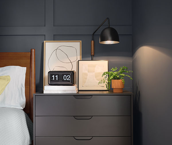 Close up of night stand table with minimalist art, clock, lamp and a plant as decoration. Table and walls are painted Cyberspace SW 7076