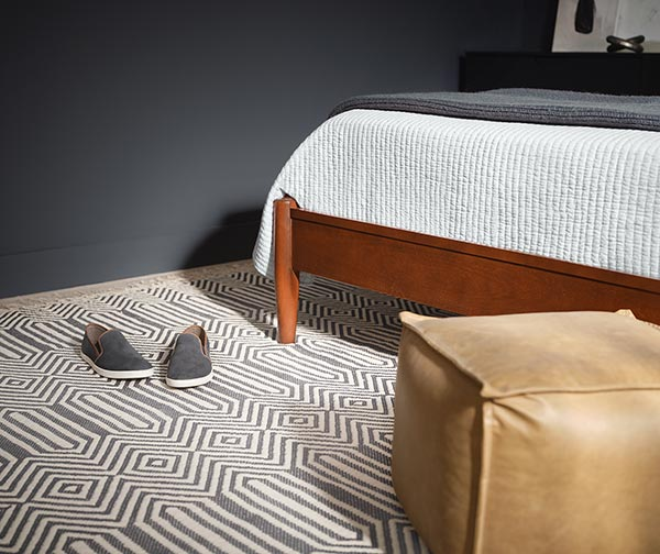Close up of cream and gray rug with shoes and floor puff sitting on the floor at the foot of the bed