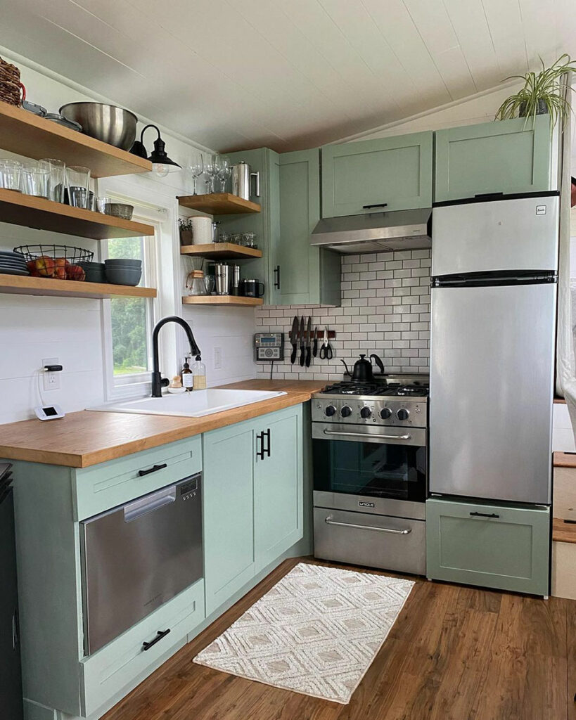 Kitchen with lower and upper cabinets painted in Coatsal Plain SW 6192.